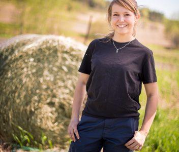 Étudiante en Gestion et technologies d'entreprise agricole debout près d'une balle de foin