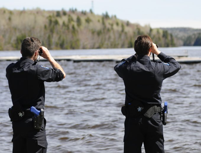 Étudiants observant le cours d'eau avec des jumelles