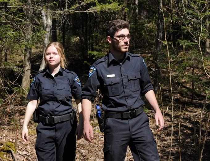 Un étudiant et une étudiante en Protection de la faune dans un sentier en forêt