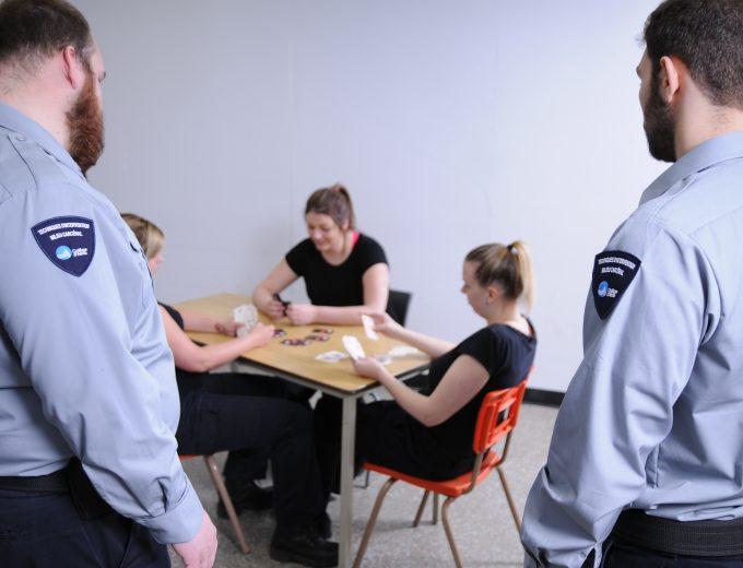 Deux étudiants en Techniques d'intervention en milieu carcéral observant 3 femmes qui jouent aux cartes