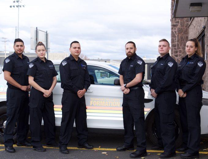 Groupe d'étudiants en Techniques policières autochtones devant une voiture balisée