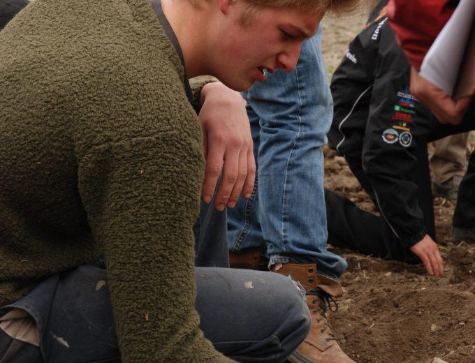 Étudiant de Gestion et technologies d'entreprise agricole qui prend une poignée de terre