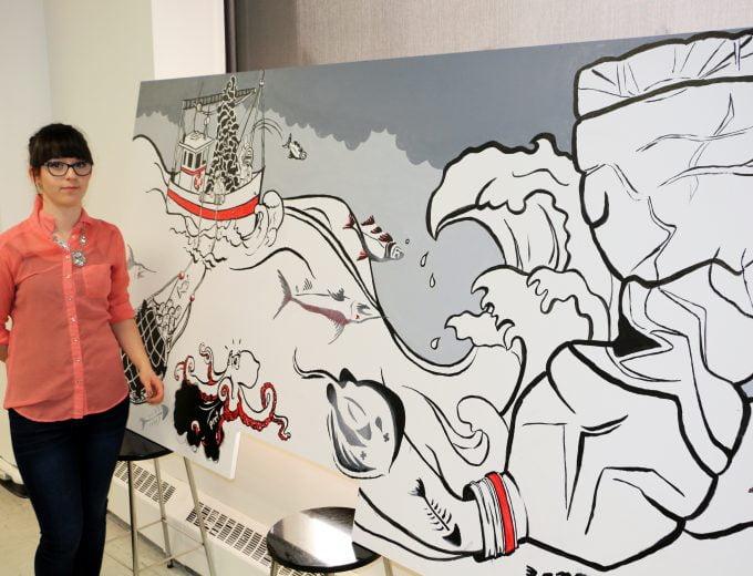 Étudiante d'Arts visuels et numériques devant son oeuvre