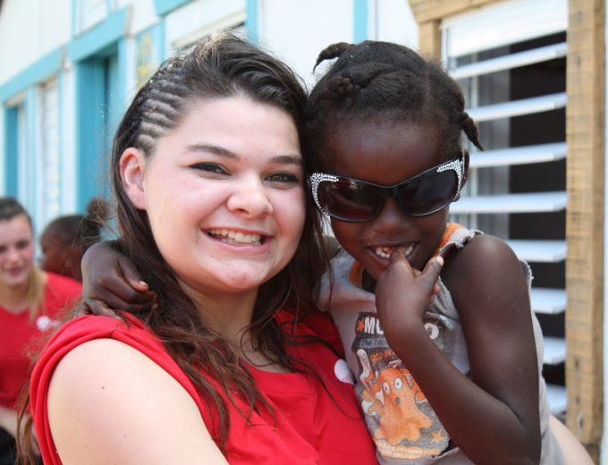 Étudiante tenant un jeune dominicain lors d'un stage en République Dominicaine
