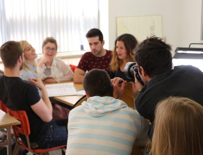 Groupe d'étudiantes et d'étudiants discutant en classe devant l'oeil du photograohe