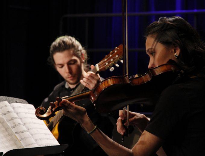 Étudiante en musique jouant du violon accompagnée d'un étudiant en guitare
