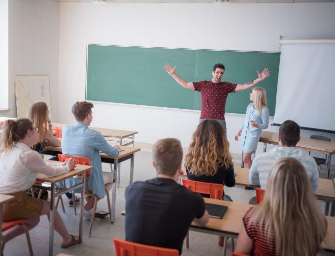 Salle de classe regroupant plusieurs étudiants écoutant le récit d'un intervenant dont les 2 bras sont soulevés