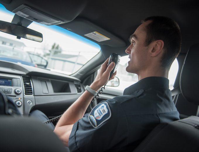 Étudiant en Techniques policières qui communique par radio dans un véhicule balisé