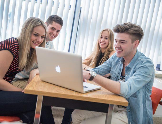 Groupe d'étudiants dans une classe qui regarde l'écran d'un portable