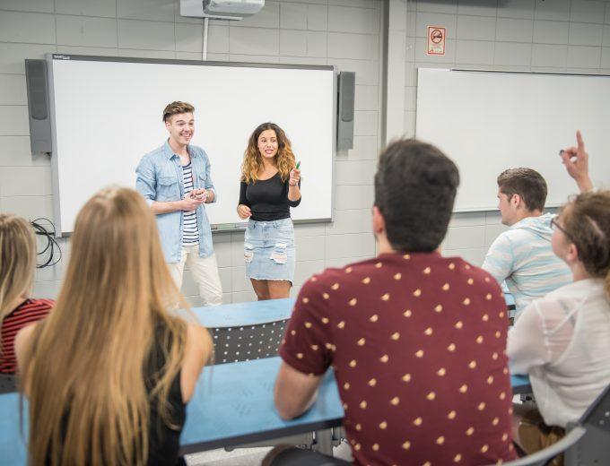 Présentation orale de 2 étudiants devant un groupe de collègues