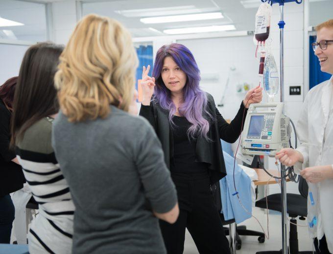 Enseignante en Soins infirmier qui donne de la formation à un groupe d'étudiantes au laboratoire de soins