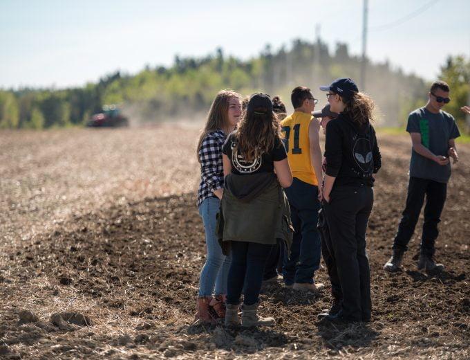 Groupe étudiante en Gestion et technologies d'entreprise agricole qui discutent dans un champ labouré