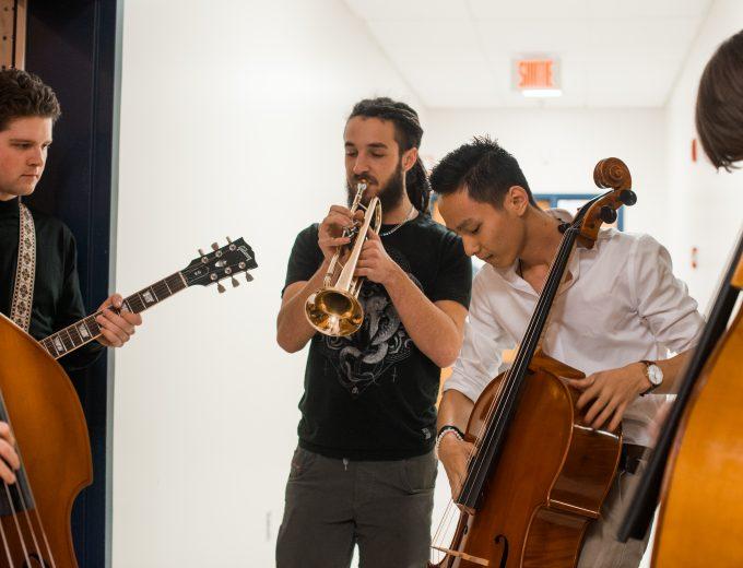 Étudiants pratiquant en groupe - guitare, contrebasse, trompette et violoncelle
