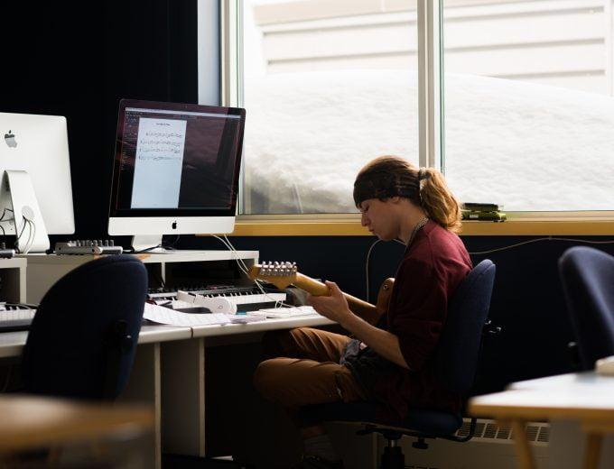 Étudiant en Musique pratiquant devant un ordinateur
