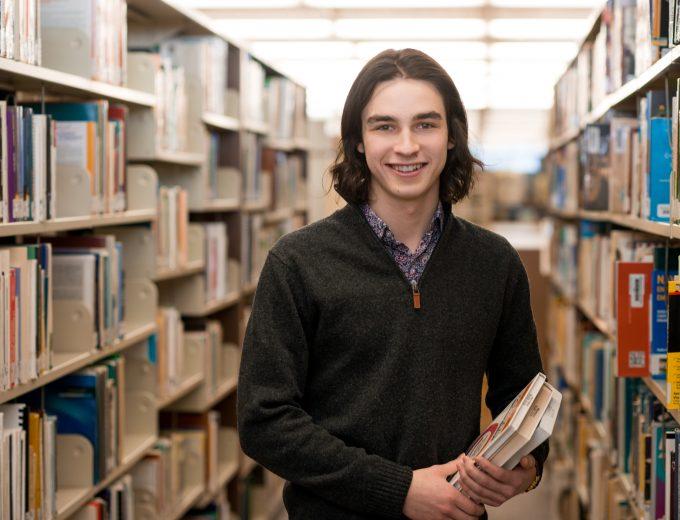 Étudiant dans les rayons de la bibliothèque du Collège