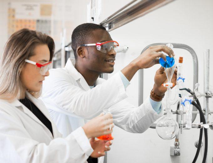 Un étudiant et une étudiante en train de faire une expérience de chimie dans un laboratoire