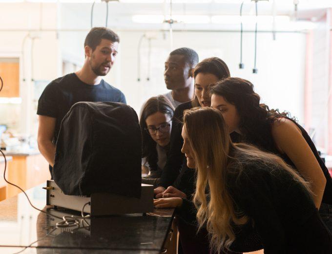 Groupe d'étudiants devant un appareil dans un laboratoire