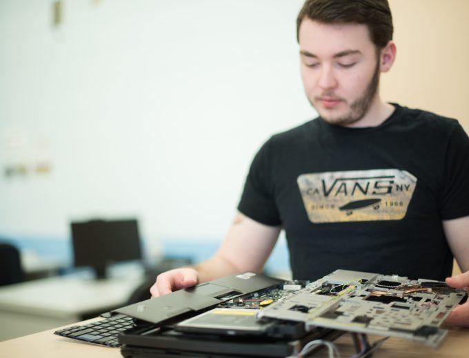 Étudiant en Techniques de l'informatique devant un ordinateur en pièces