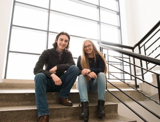 Un étudiant et une étudiante assis dans l'escalier central du Collège
