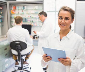Jeune femme dans un laboratoire de pharmacie en compagnie de 2 collègues masculins
