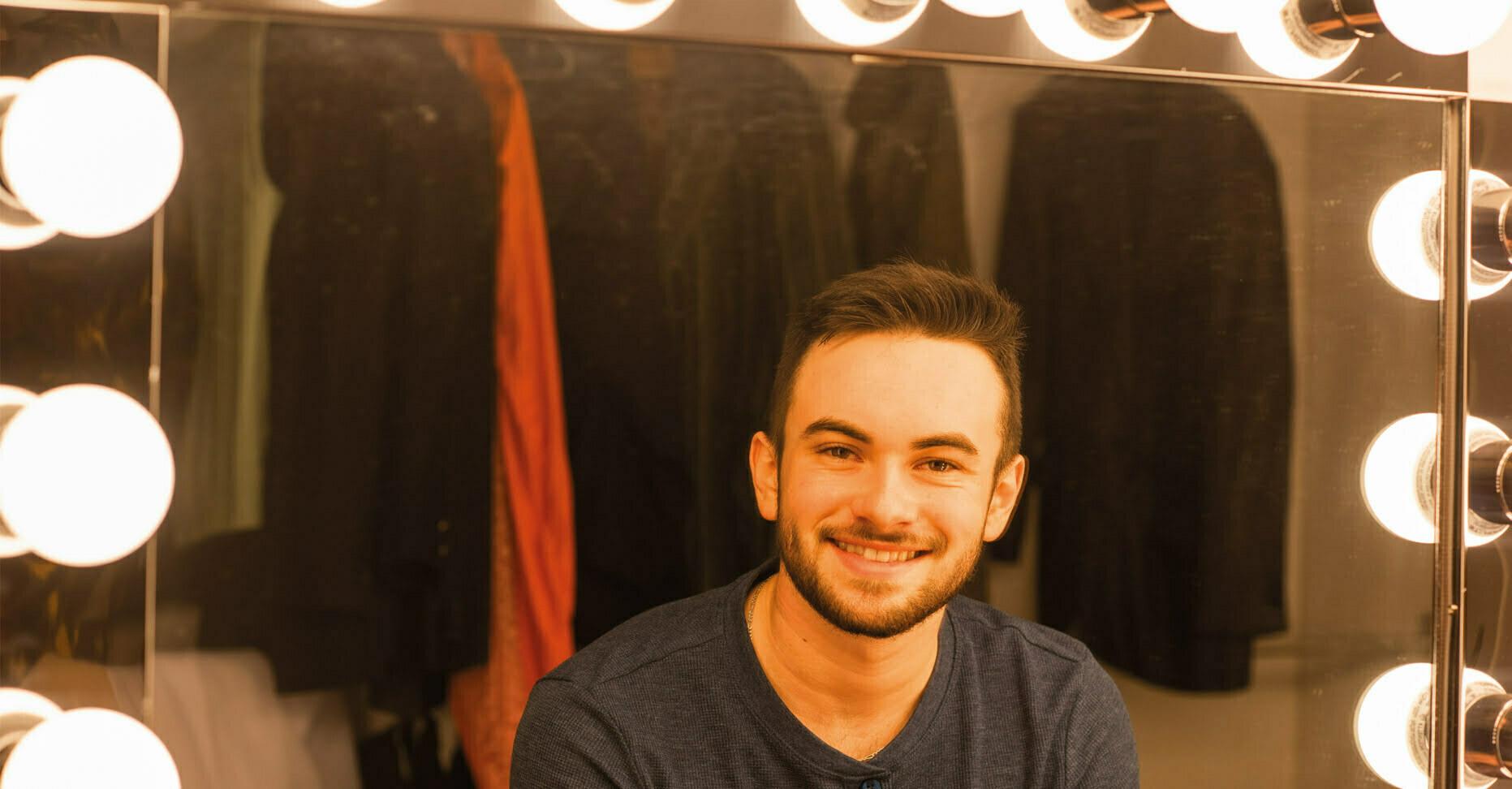Étudiant assis devant un miroir dans une loge